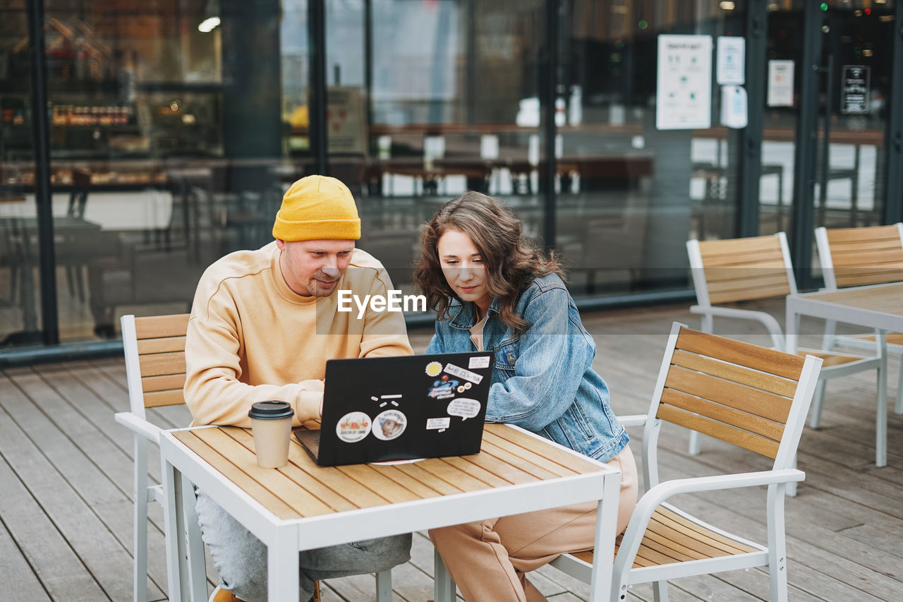 Stylish young couple freelancers working on laptop in street cafe