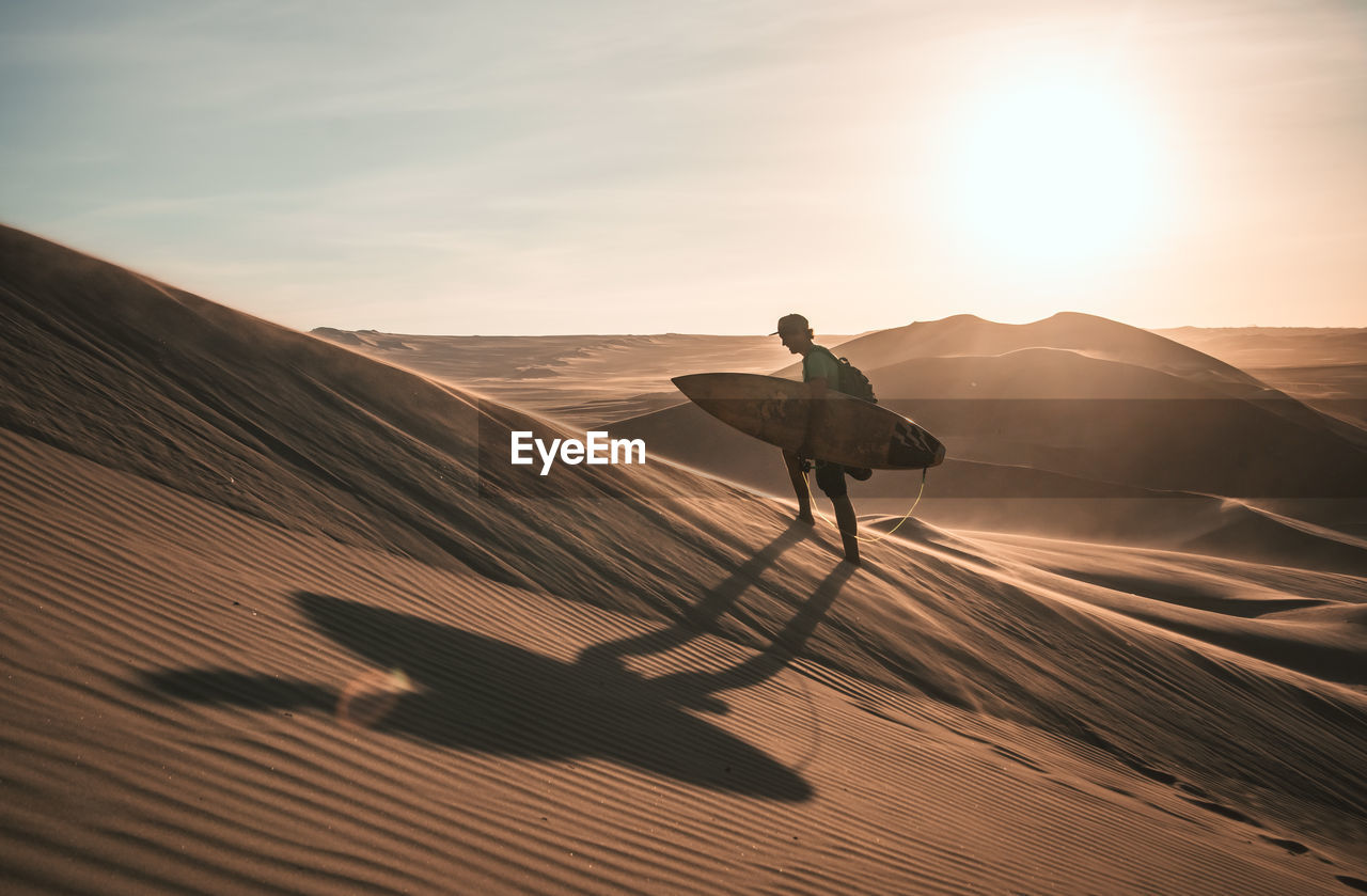 sky, sunlight, real people, desert, one person, scenics - nature, beauty in nature, nature, shadow, full length, land, lifestyles, leisure activity, sand, sand dune, mountain, tranquil scene, non-urban scene, landscape, arid climate, climate, lens flare, sun, outdoors