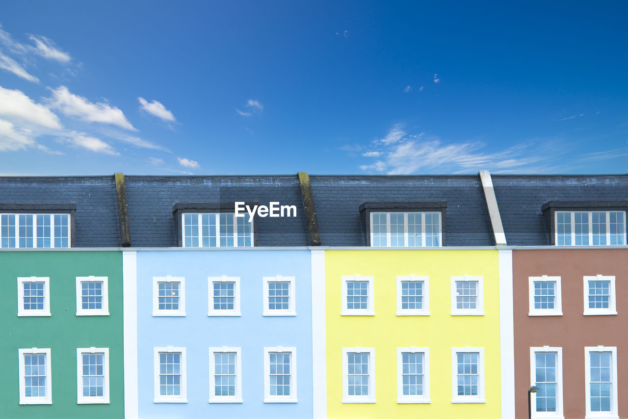 Multi colored buildings against blue sky