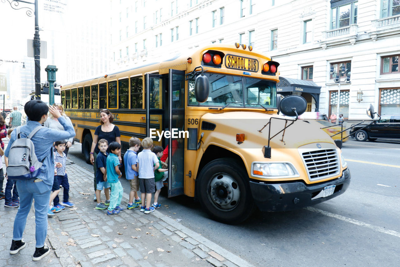 transportation, street, school bus, land vehicle, bus, real people, mode of transport, education, walking, public transportation, building exterior, women, men, day, built structure, outdoors, lifestyles, architecture, student, city, people