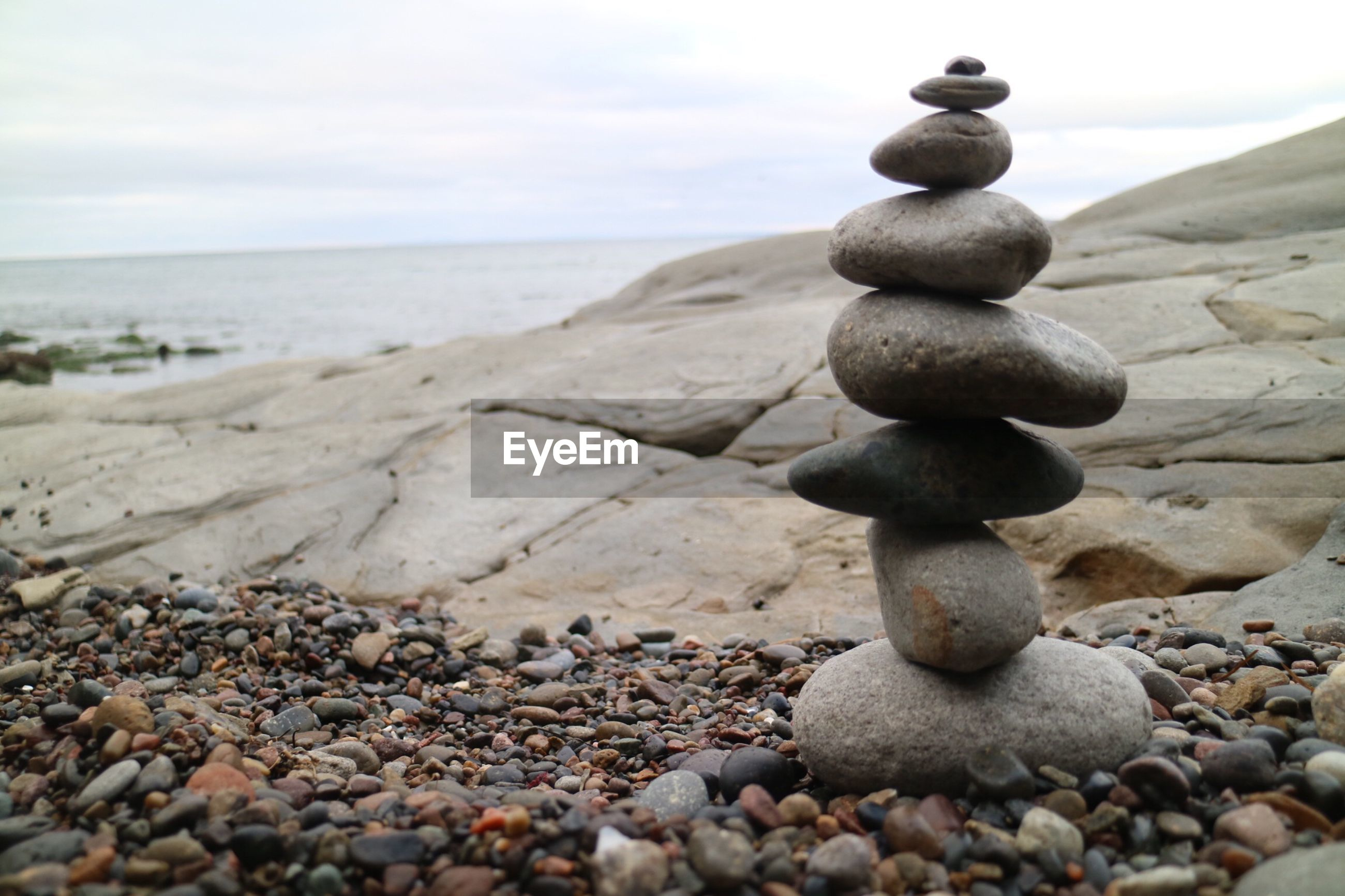Stack of stones at beach against sky