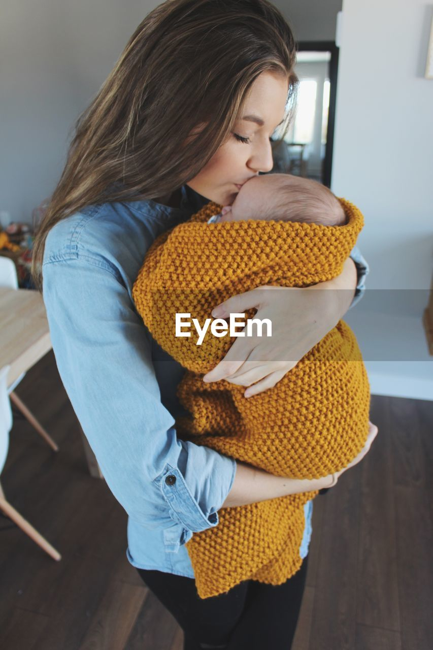 Young Woman Holding Baby At Home