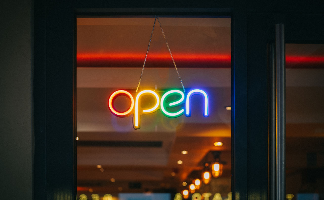 LOW ANGLE VIEW OF ILLUMINATED SIGN ON GLASS WINDOW