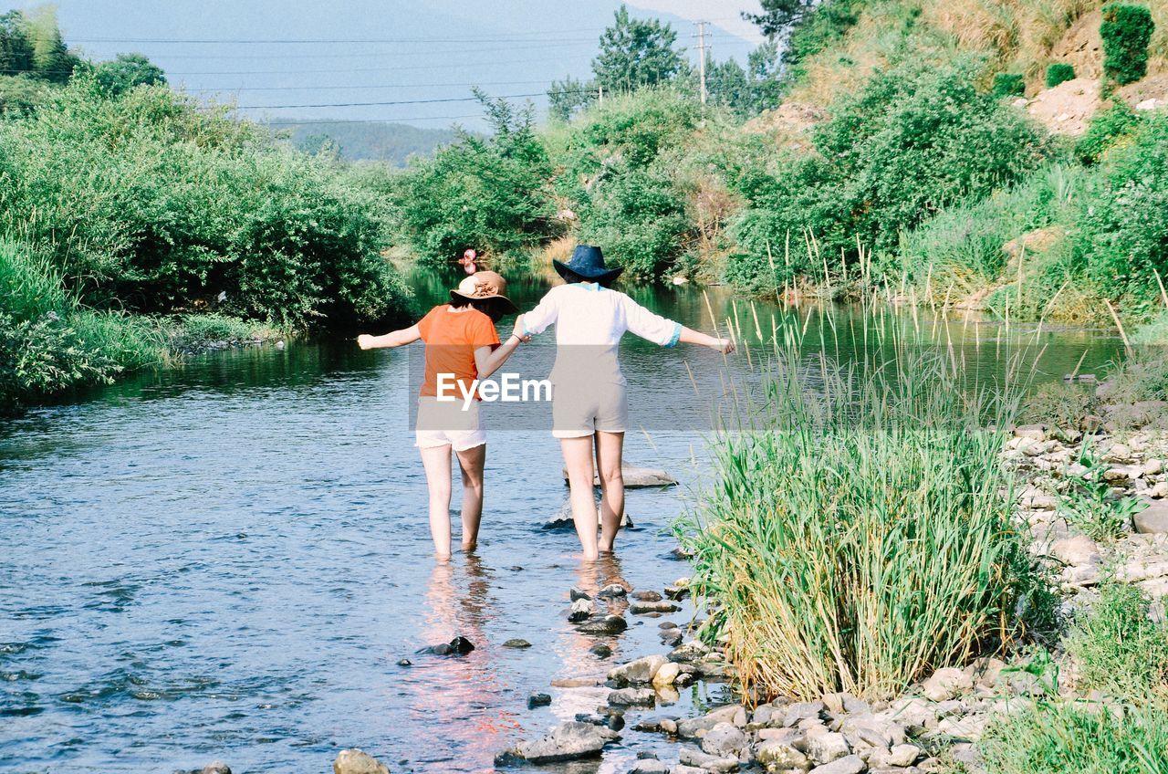 Friends Standing In Water