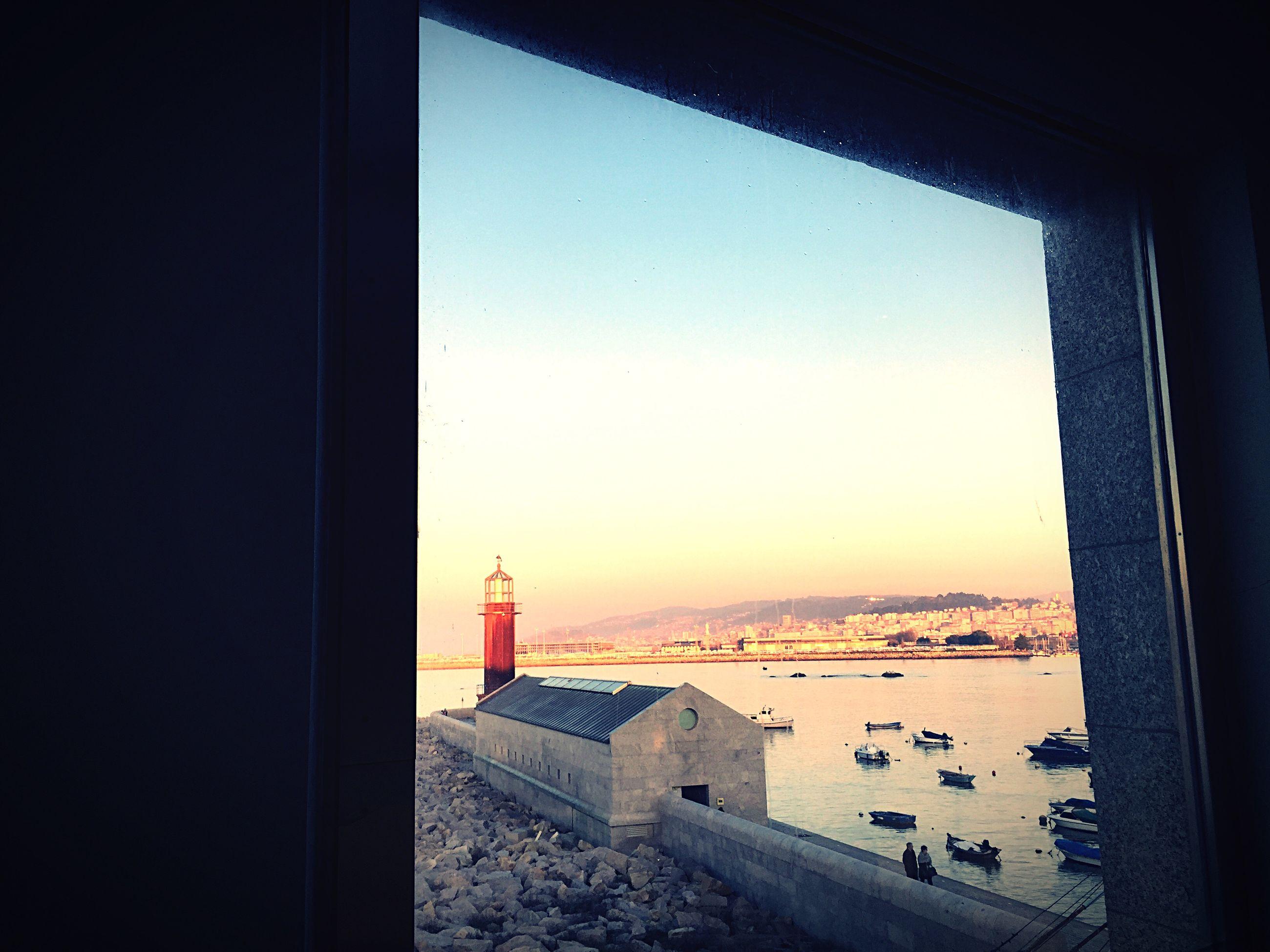 Sea by city against clear sky seen through window