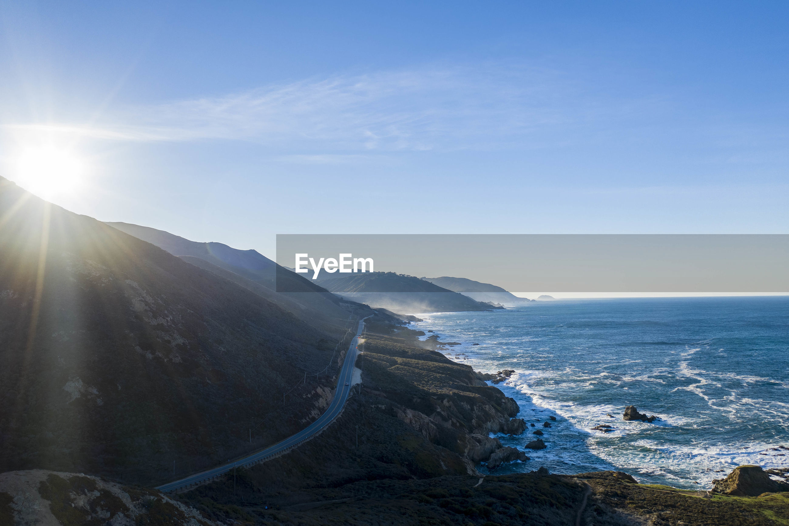 SCENIC VIEW OF SEA AND MOUNTAINS AGAINST BRIGHT SUN