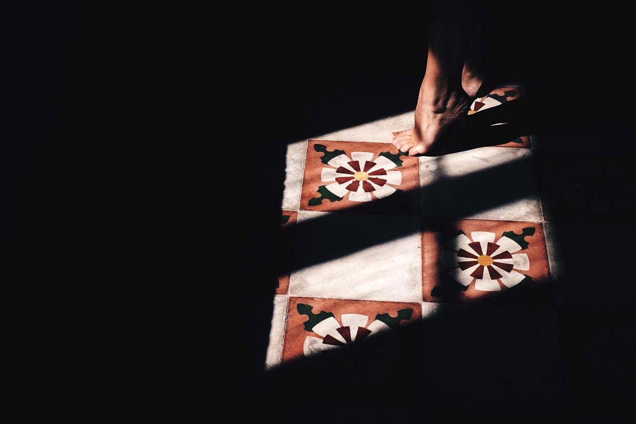 Low Section Of Woman Tiptoeing On Floor In Darkroom