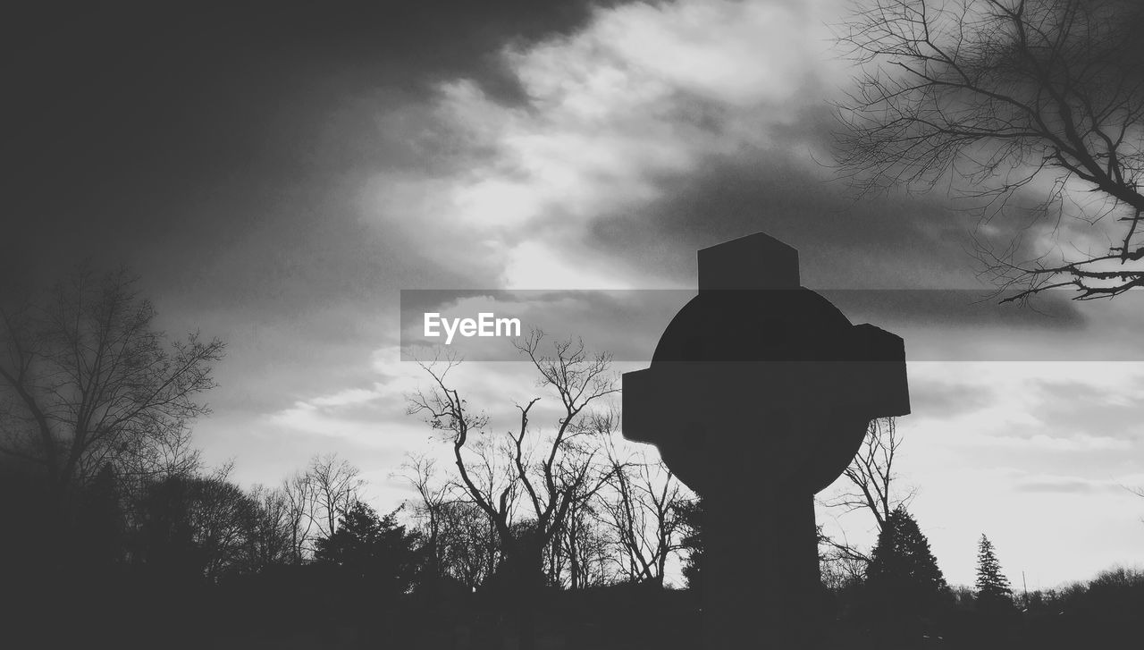 Silhouette tombstone on field against sky at dusk