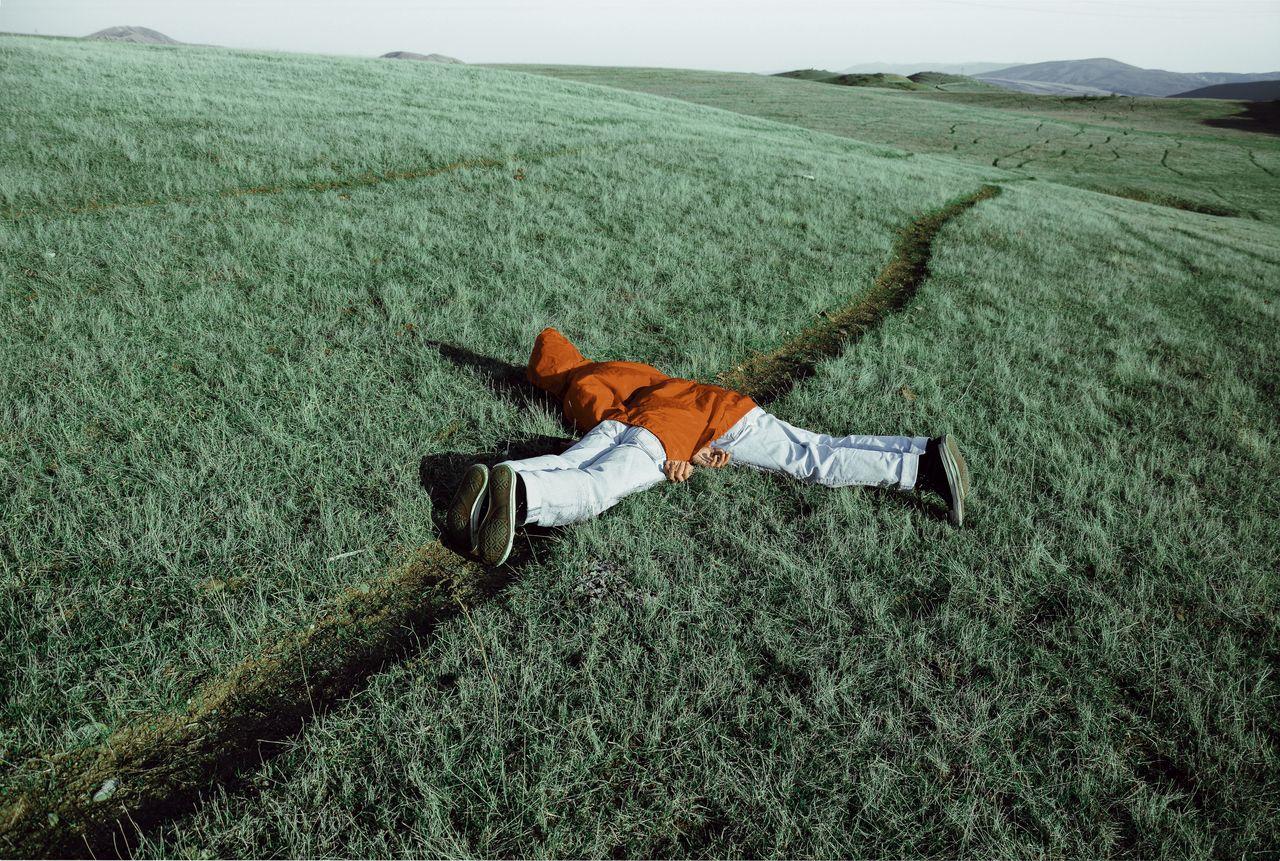 Men Lying On Grassy Field Against Sky