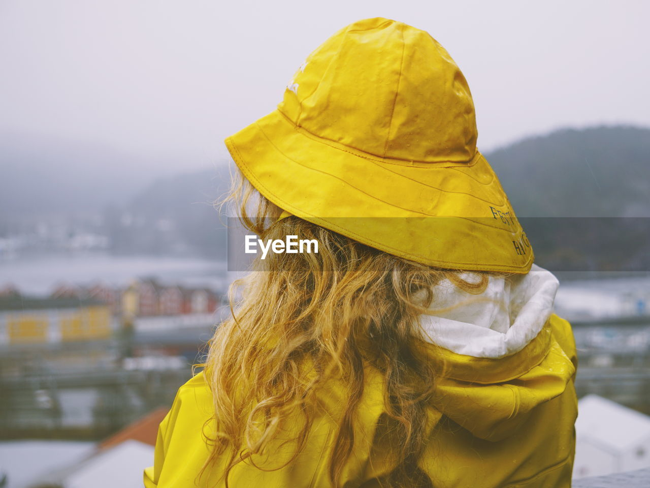 Rear View Of Woman In Yellow Warm Clothing Against Sky