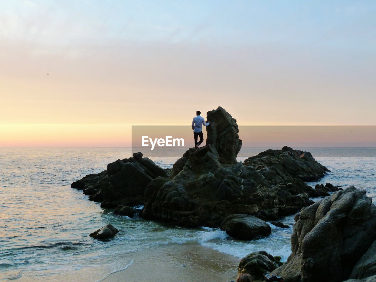 View Of Man Standing On Cliff At Beach During Sunset