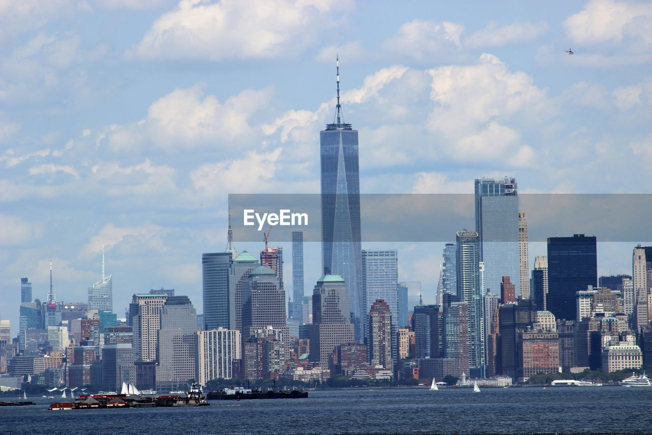 skyscraper, architecture, building exterior, built structure, tall - high, city, tower, modern, cloud - sky, travel destinations, urban skyline, sky, waterfront, cityscape, financial district, skyline, downtown district, day, water, tall, growth, outdoors, no people