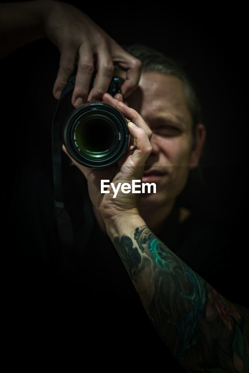 holding, real people, human hand, indoors, hand, men, one person, photography themes, technology, camera - photographic equipment, occupation, lifestyles, tattoo, activity, black background, skill, leisure activity, human body part, creativity, digital camera