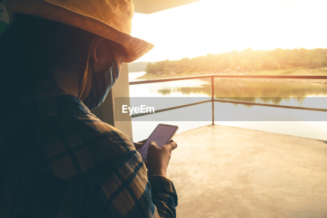 MAN USING SMART PHONE BY LAKE
