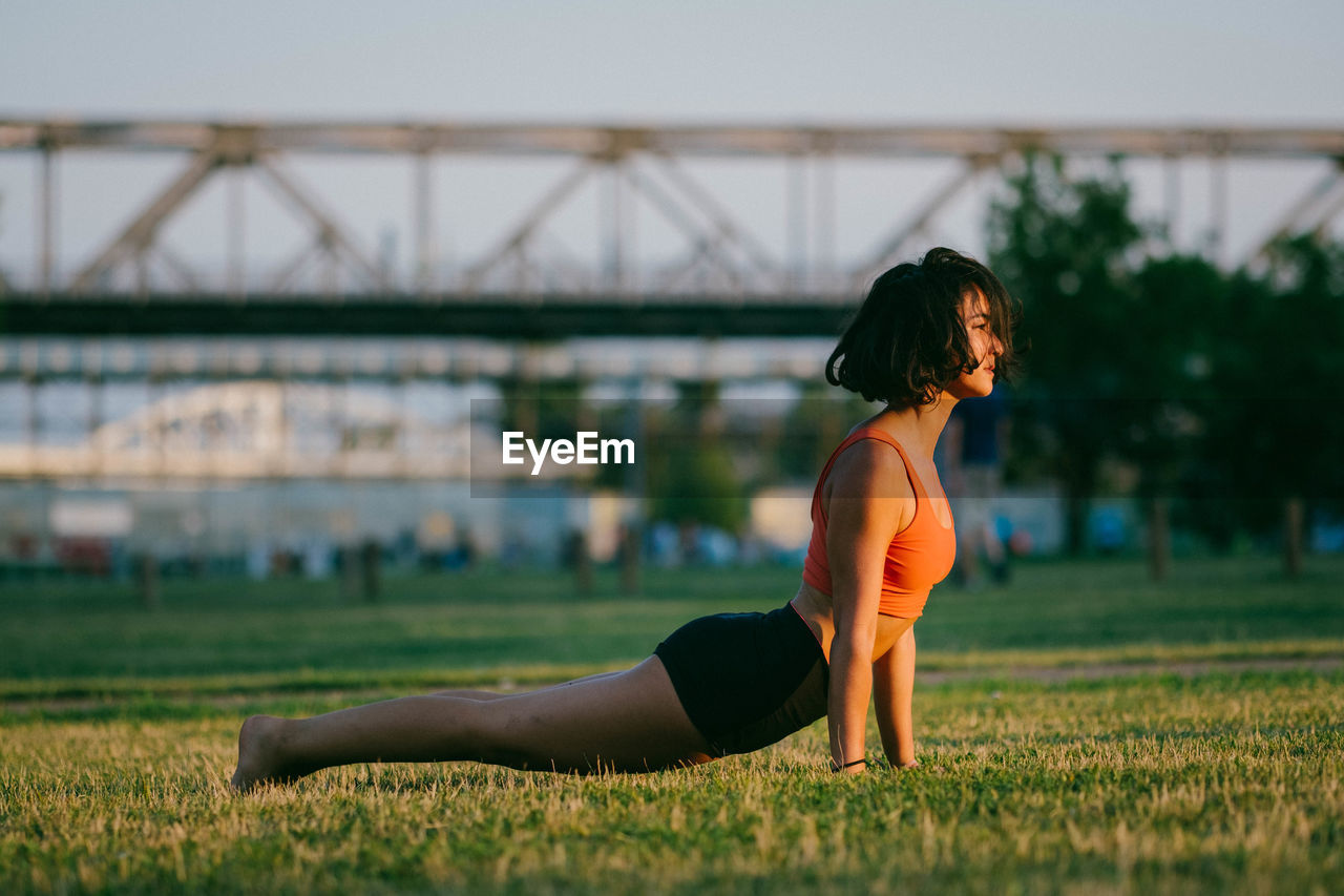 Woman exercising on grassy field