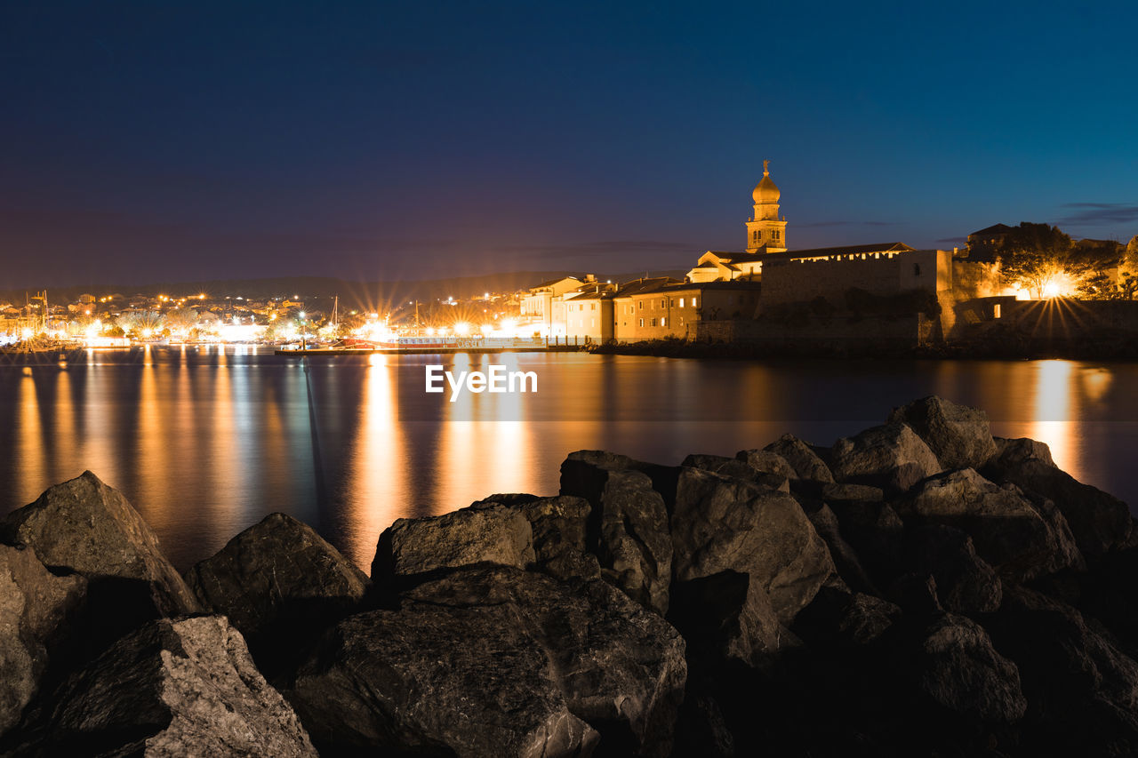 water, building exterior, built structure, architecture, sky, illuminated, rock, rock - object, solid, nature, no people, night, city, reflection, building, river, religion, travel destinations, place of worship, outdoors