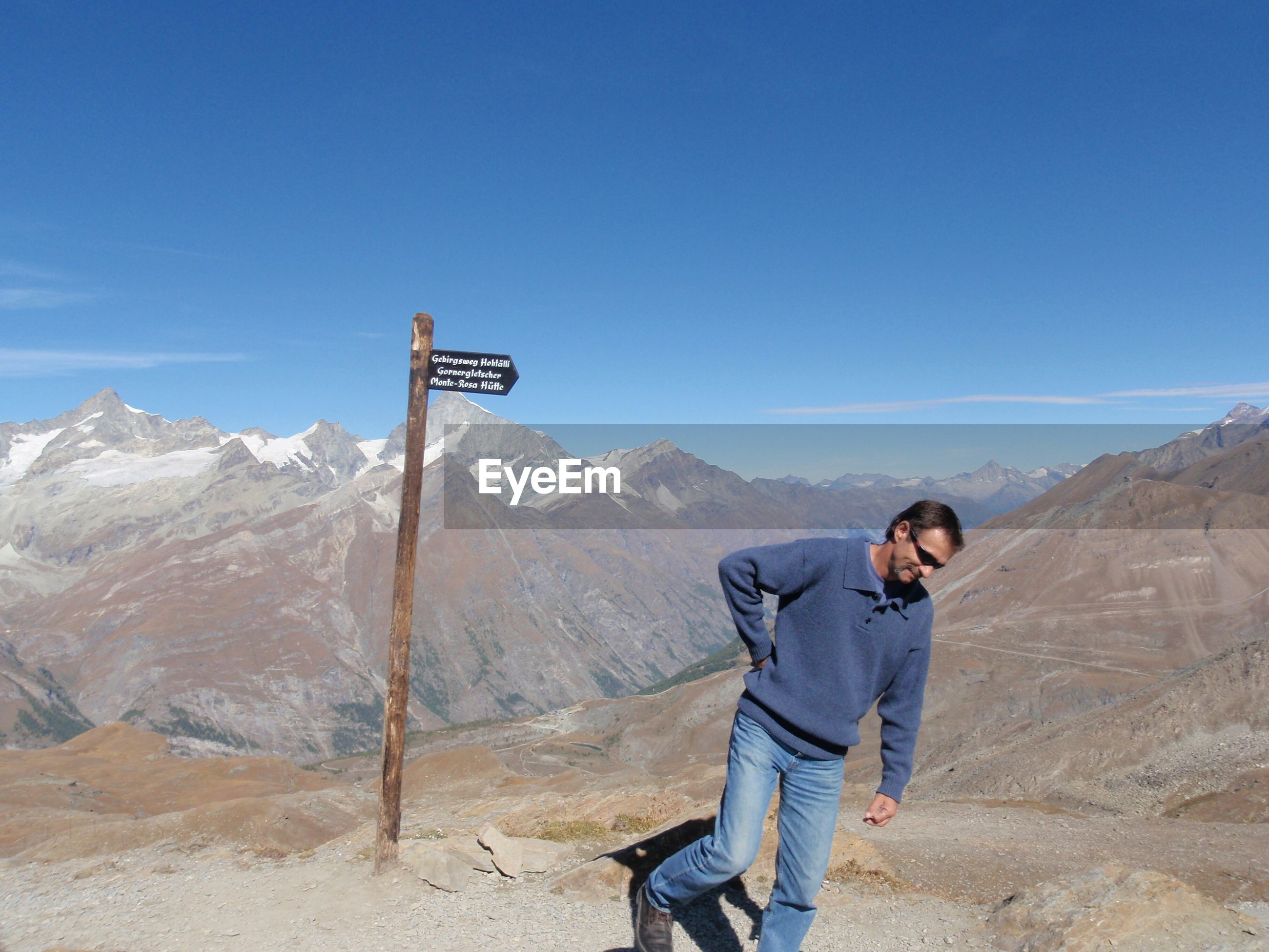 Man walking by information sign on mountain against sky