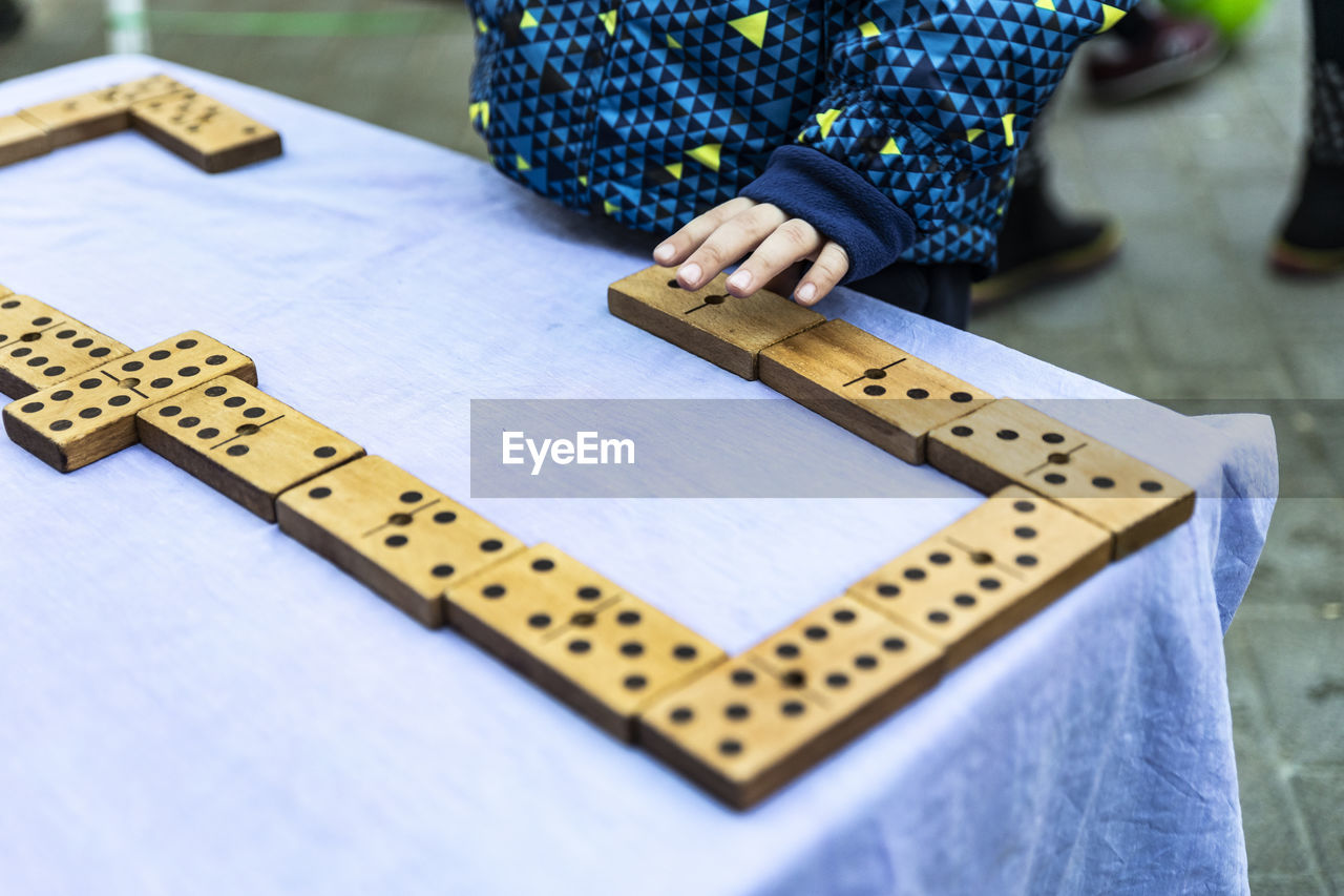 Midsection Of Child Playing With Toy Blocks On Table