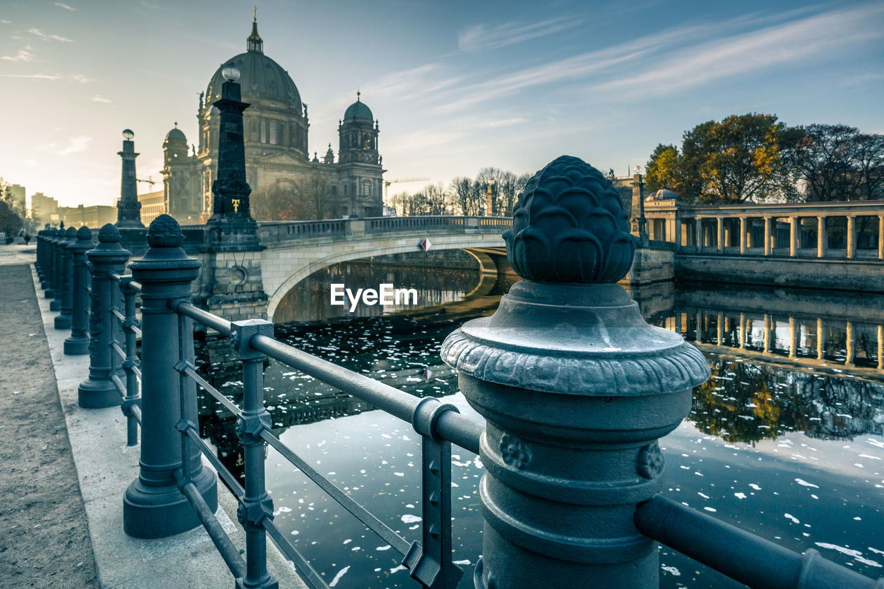 Railing By Spree River Against Berlin Cathedral
