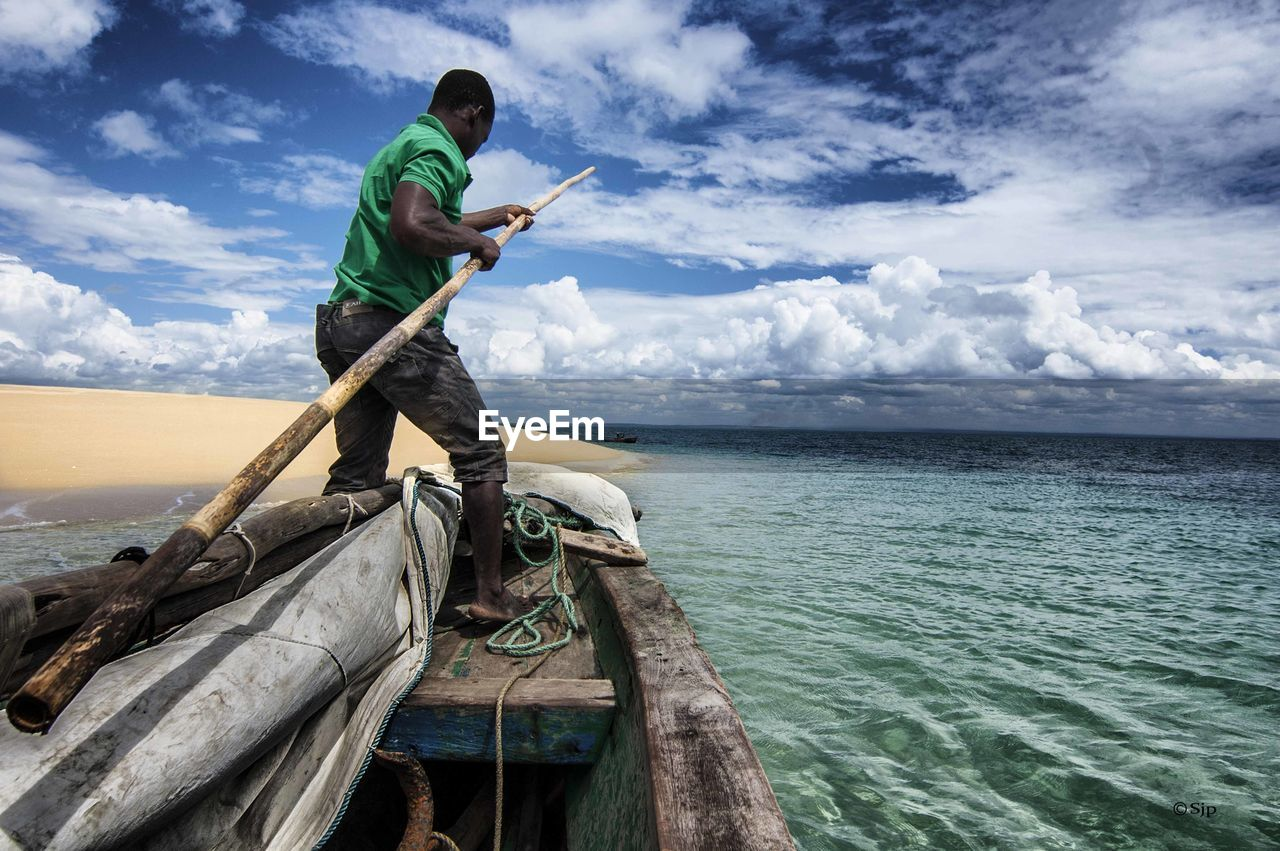 sky, cloud - sky, horizon over water, sea, water, fishing, nature, one person, full length, side view, beauty in nature, holding, standing, outdoors, day, fisherman, real people, scenics, men, young adult, fishing pole, adult, people