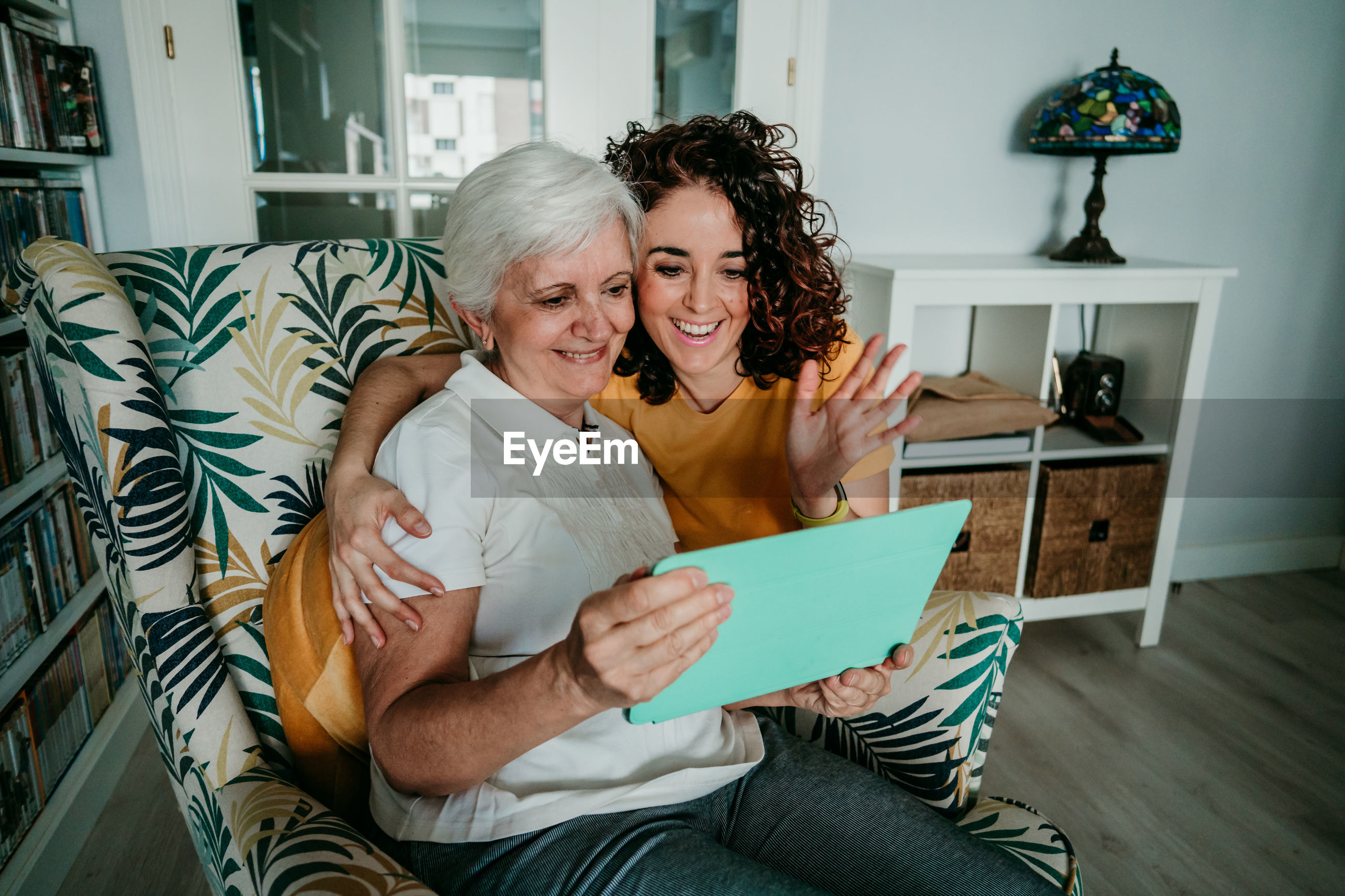 Smiling woman and daughter on video call over digital tablet