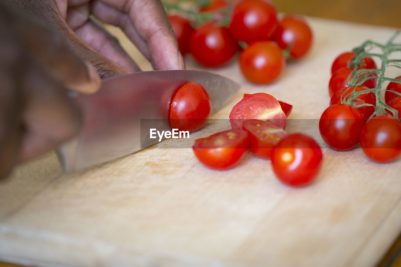 Cropped Image Of Hands Cutting Cherry Tomatoes On Board