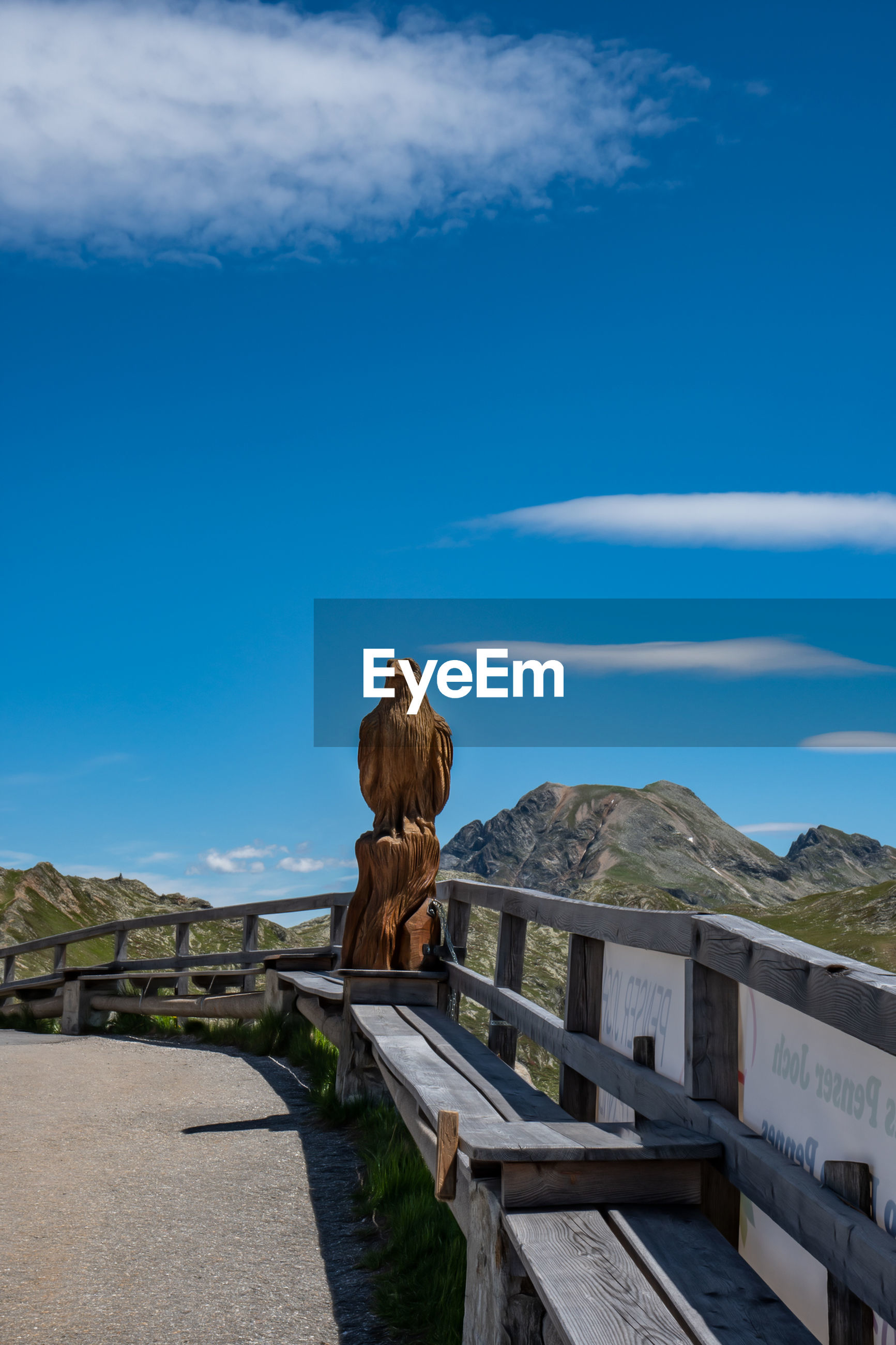 sky, day, nature, cloud - sky, mountain, blue, rear view, one person, real people, direction, wood - material, full length, leisure activity, beauty in nature, lifestyles, tranquil scene, architecture, tranquility, women