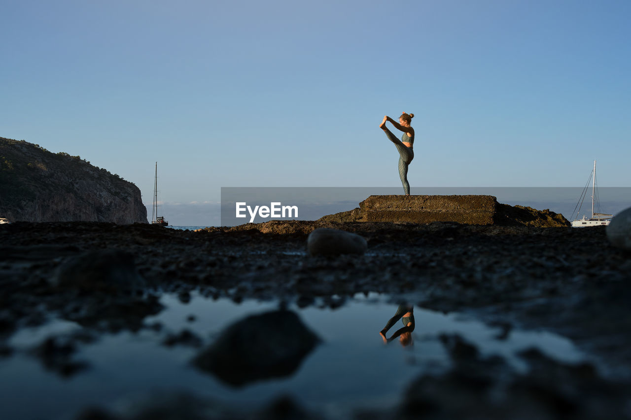 MAN STANDING ON ROCK BY WATER AGAINST SKY