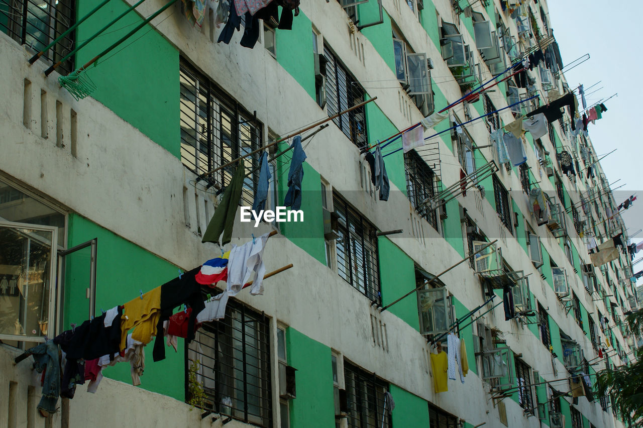 building exterior, built structure, architecture, low angle view, building, hanging, day, no people, outdoors, residential district, flag, city, multi colored, nature, decoration, sky, bunting, clothing, laundry, window, light, apartment