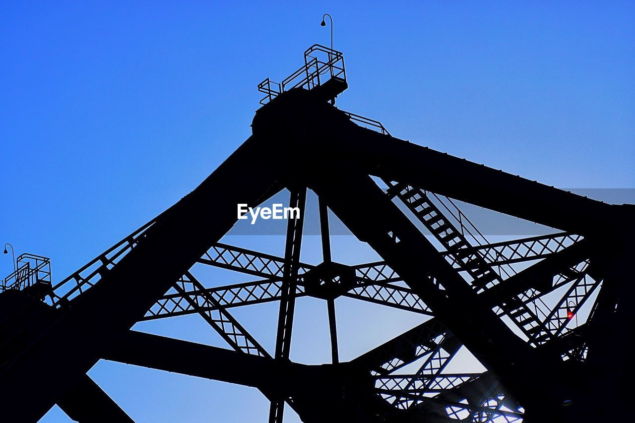 sky, low angle view, blue, silhouette, architecture, clear sky, metal, nature, machinery, built structure, no people, industry, outdoors, day, construction industry, copy space, crane - construction machinery, tall - high, development, arts culture and entertainment