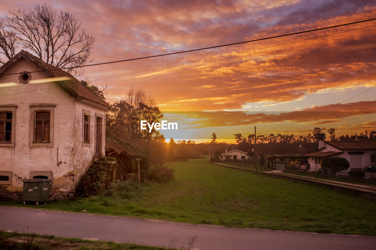 built structure, architecture, building exterior, sunset, sky, house, orange color, no people, cloud - sky, tree, outdoors, residential building, bare tree, nature, beauty in nature, grass, day