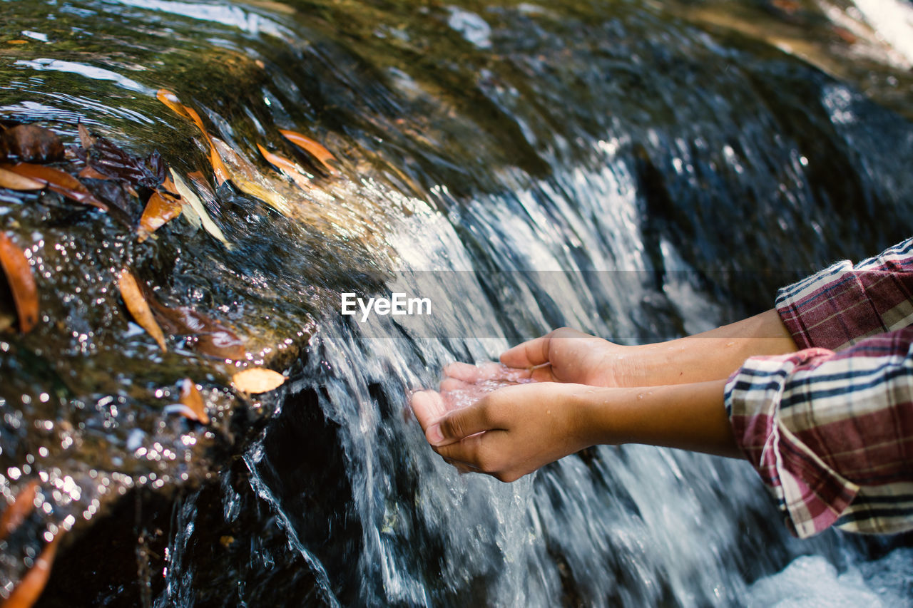 Cropped Image Of Person With Hands Cupped By Waterfall
