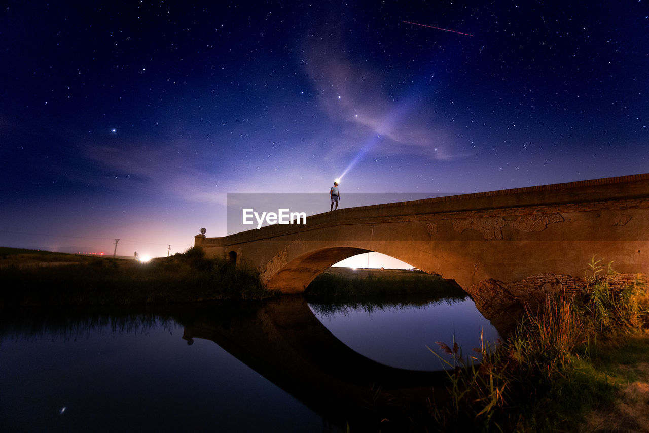 Man Flashing Light On Arch Bridge Over River Against Sky At Night
