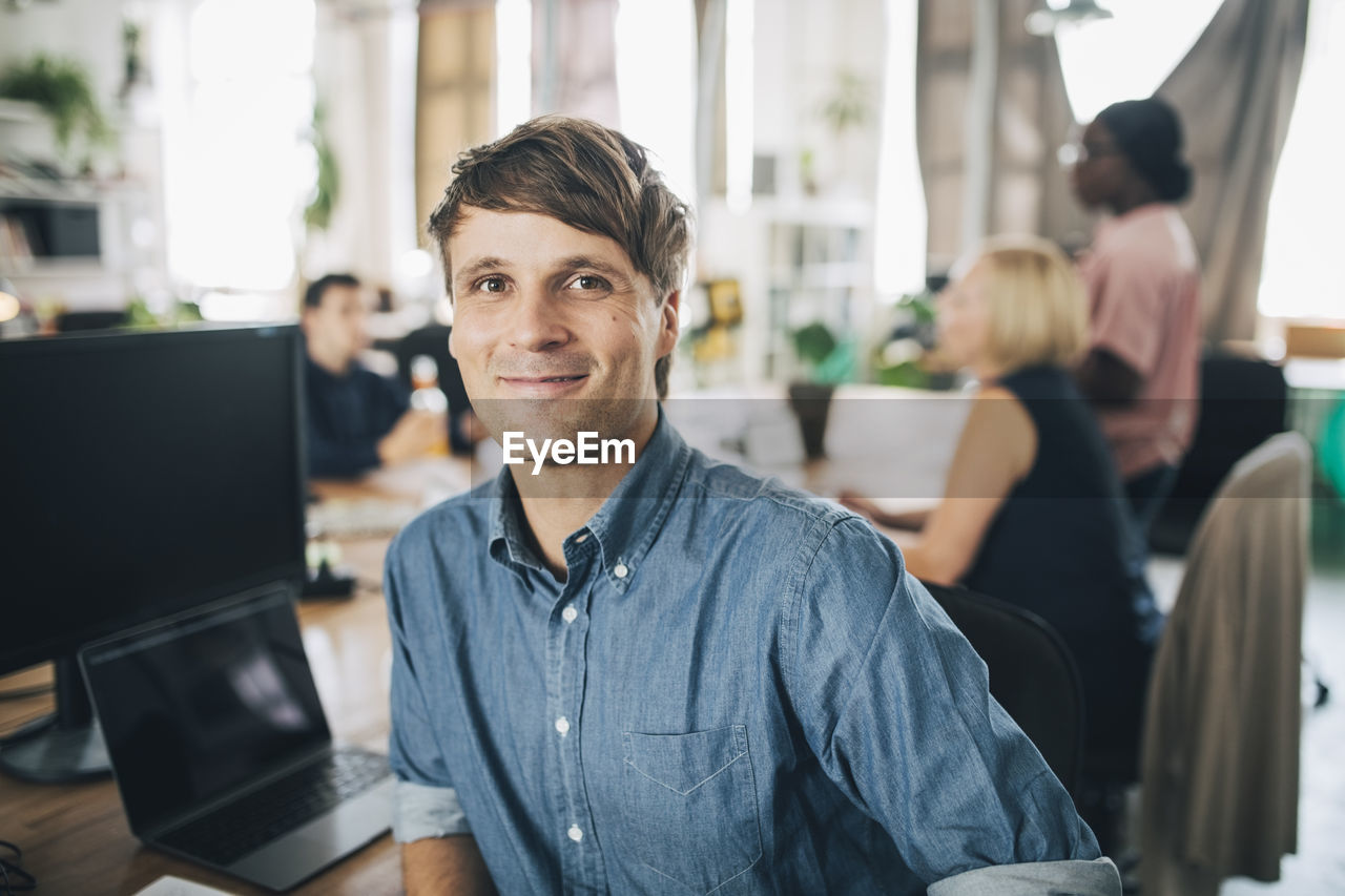 looking at camera, computer, portrait, men, technology, sitting, indoors, office, smiling, focus on foreground, casual clothing, table, business, people, young adult, real people, young men, connection, adult, new business, coworker