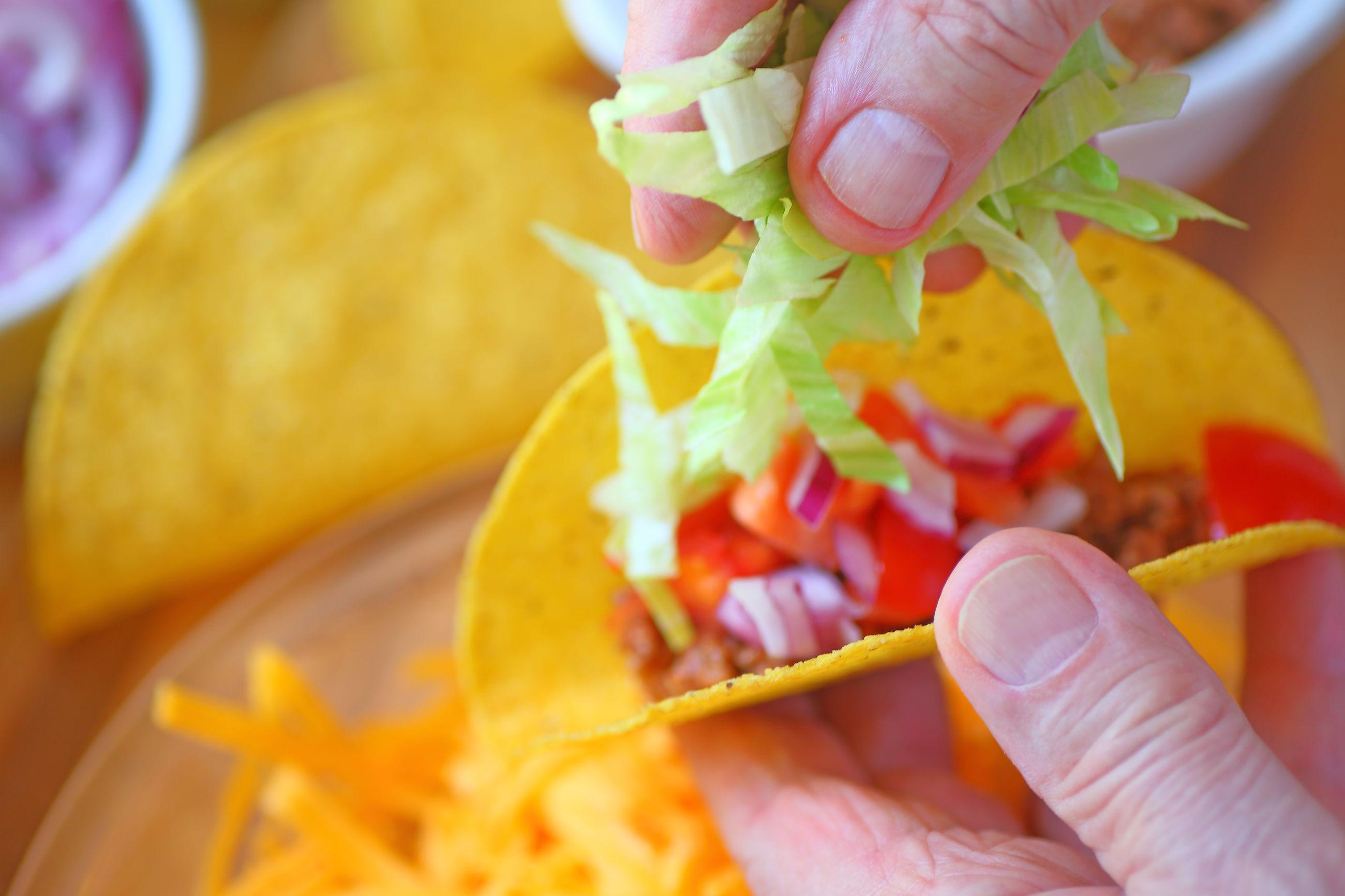 Close-up of hand holding preparing taco