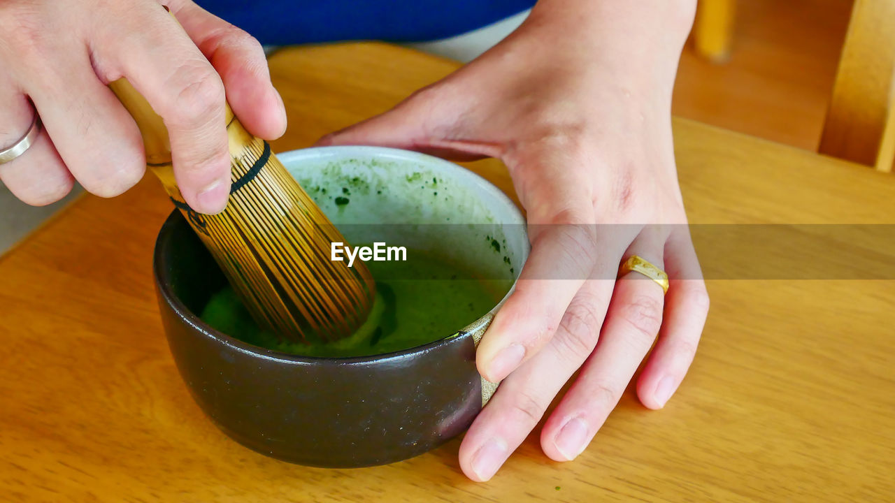 Cropped Hands Of Woman Mixing Soup In Bowl On Table