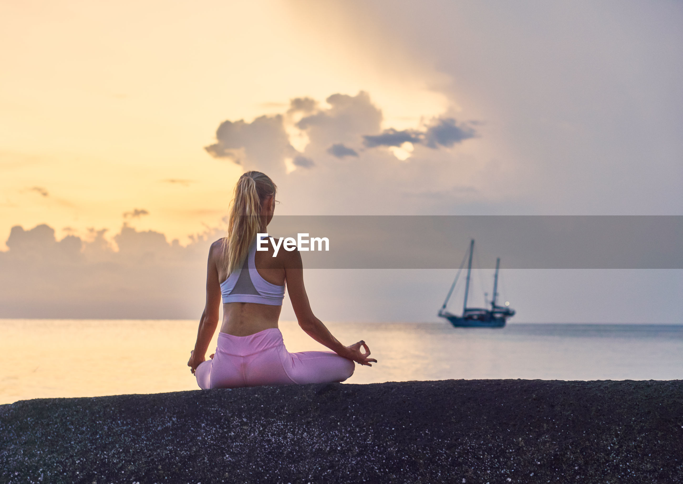 Rear view of woman mediating while sitting at beach against sky during sunset