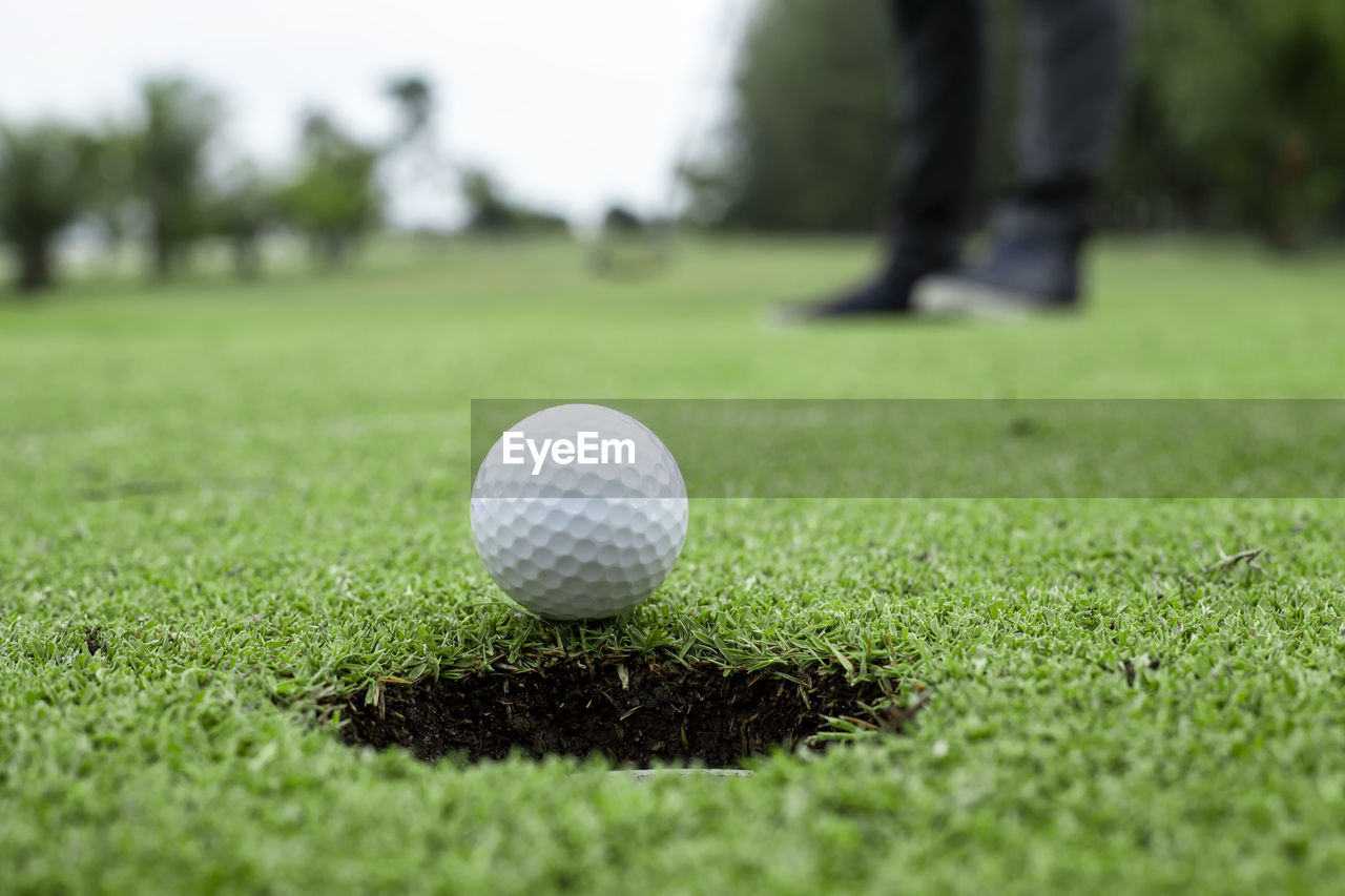 Low section of man by golf ball at course