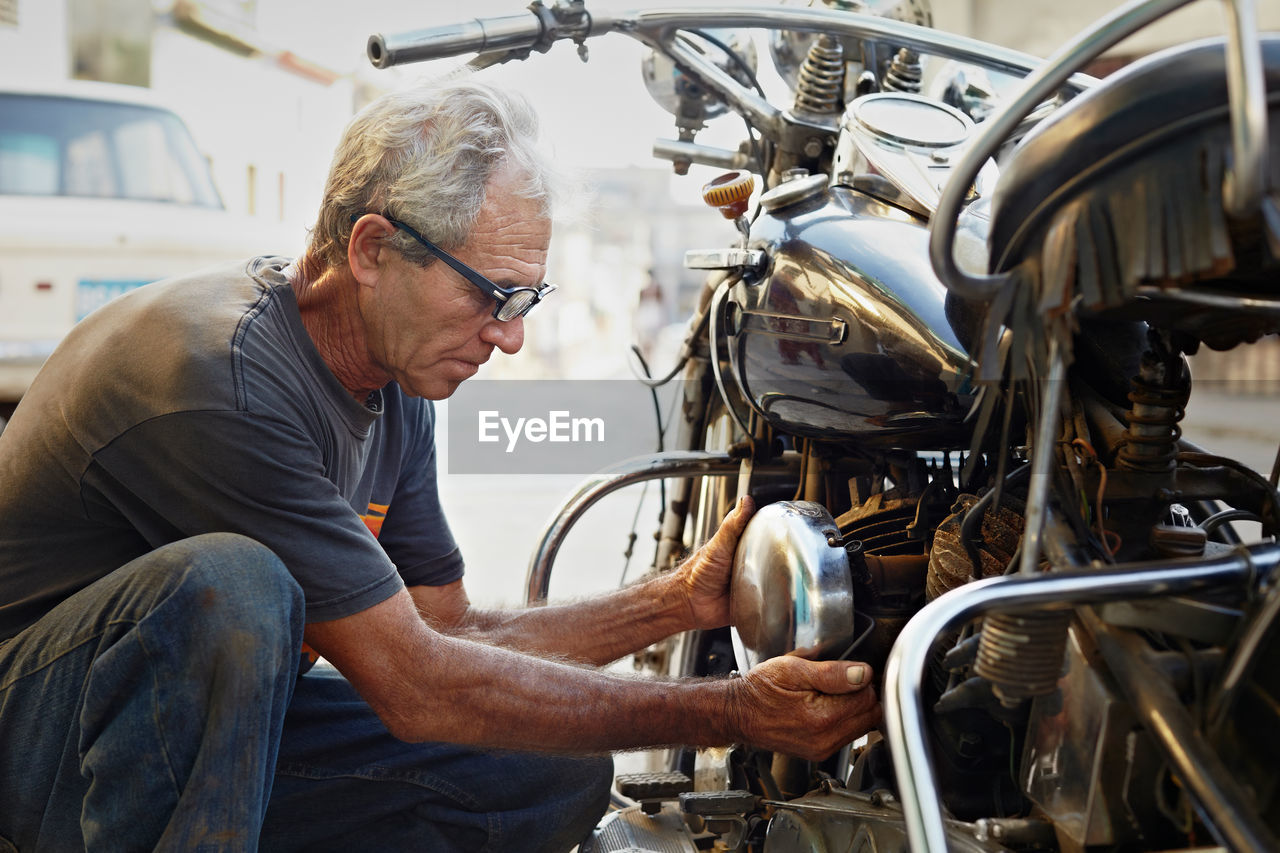 Side view of senior man repairing motorcycle outdoors