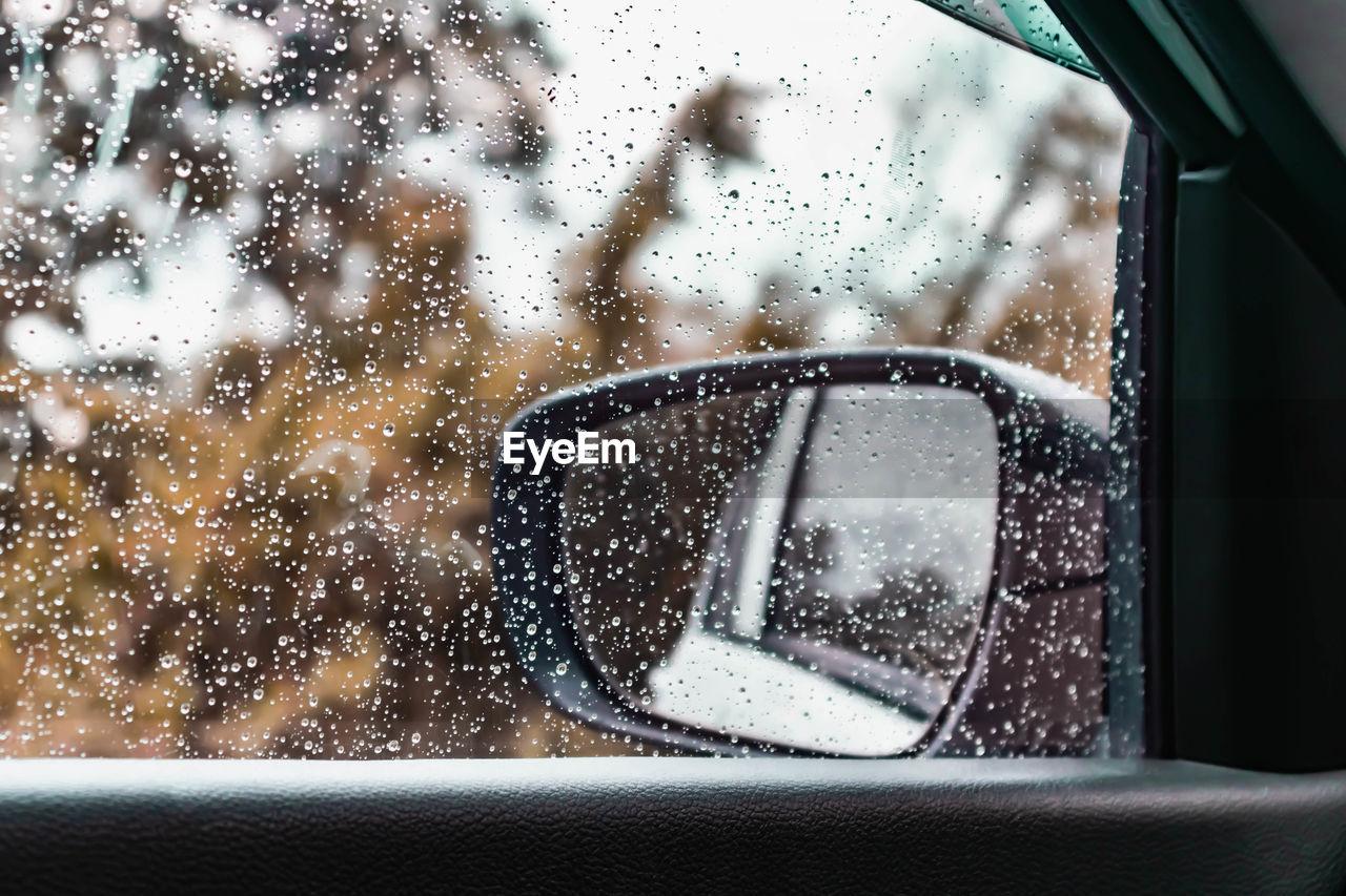 Side-view mirror seen through wet car window during rainy season