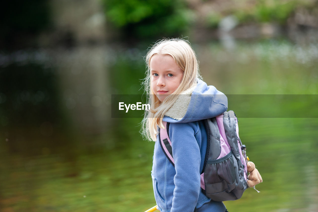 Portrait of girl standing against lake