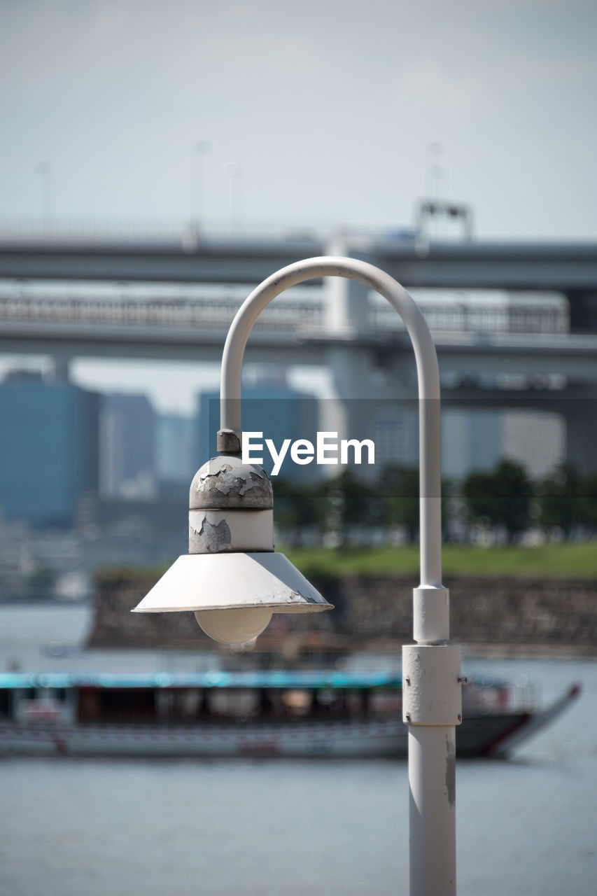 focus on foreground, built structure, architecture, day, building exterior, no people, metal, outdoors, lighting equipment, close-up, nature, sky, hanging, white color, city, water, representation, security, safety, design, silver colored