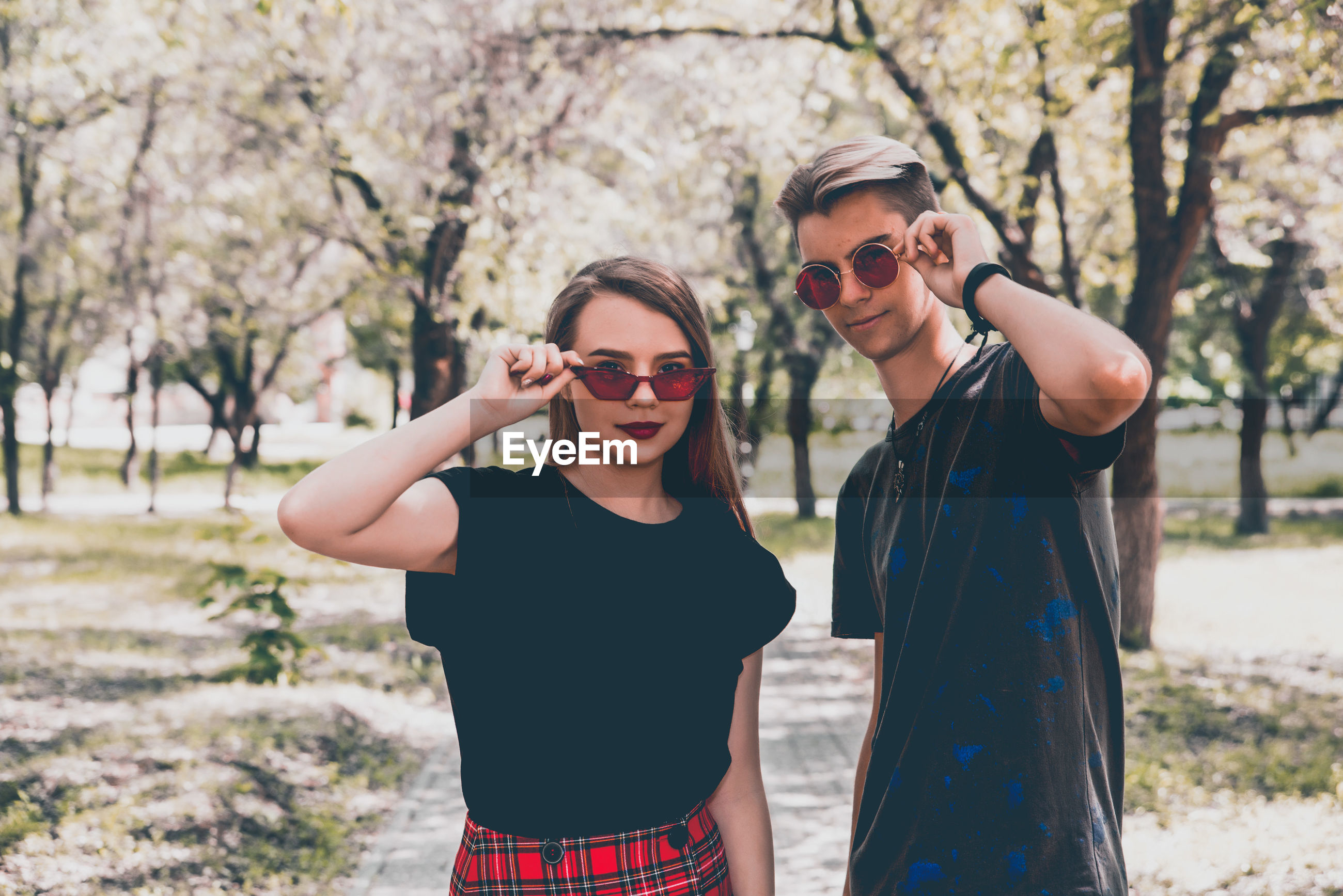 Couple wearing sunglasses standing against trees