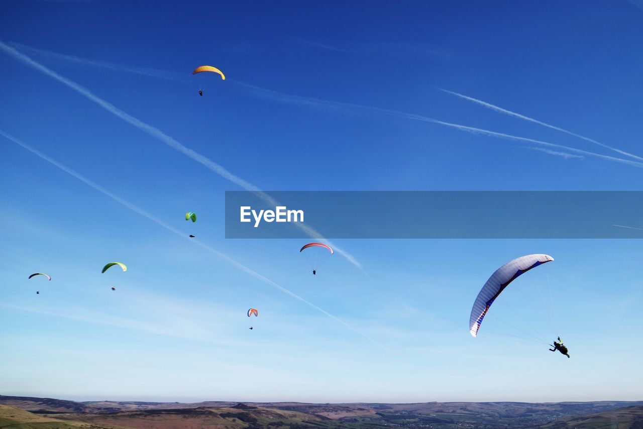 flying, adventure, extreme sports, sport, mid-air, parachute, sky, blue, paragliding, freedom, leisure activity, unrecognizable person, nature, low angle view, beauty in nature, cloud - sky, day, multi colored, real people, transportation, outdoors, vapor trail, kiteboarding