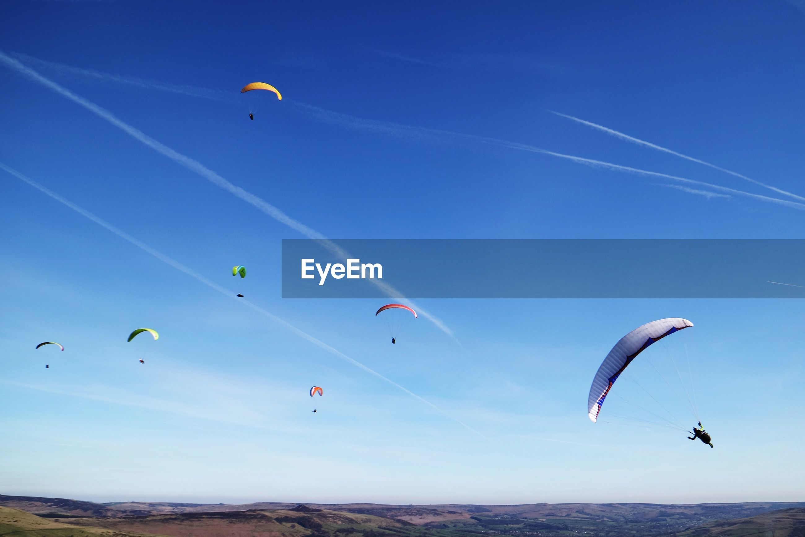 Low angle view of people paragliding against blue sky