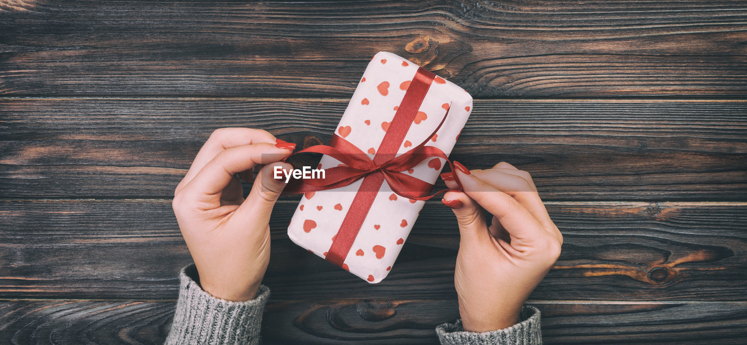 Cropped hands of woman opening gift on table