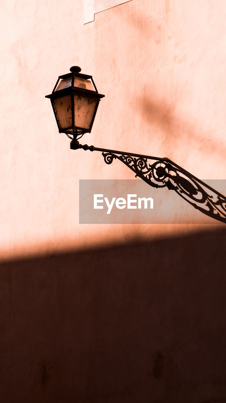 LOW ANGLE VIEW OF LAMP POST ON WALL