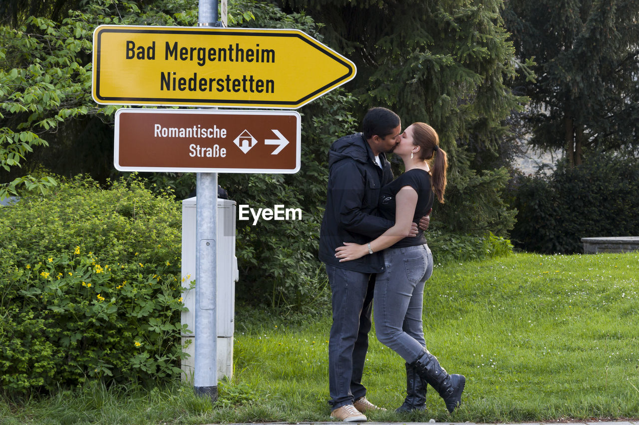 Side view full length of couple kissing by information sign on grassy field
