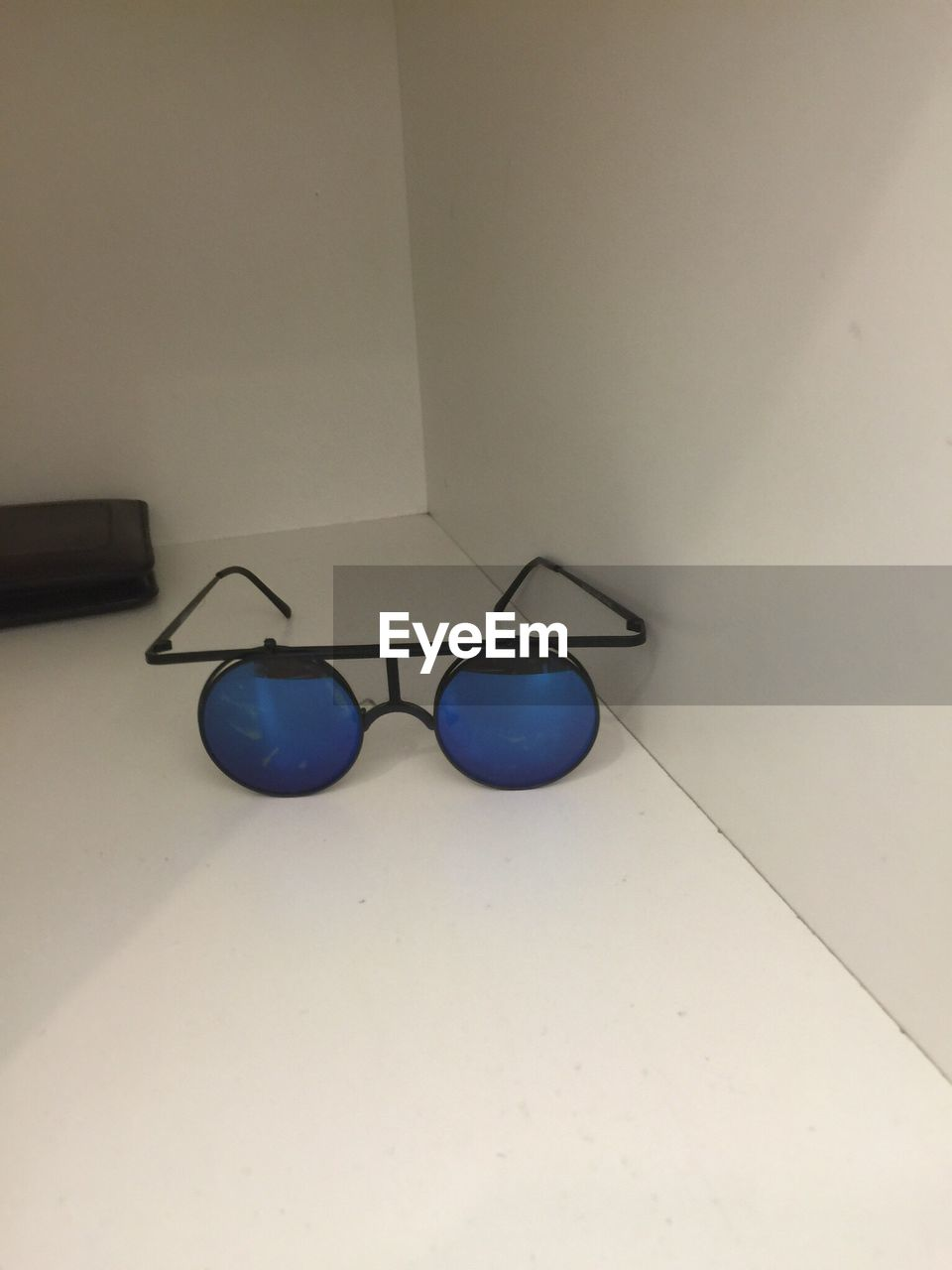 High angle view of blue sunglasses on floor against wall