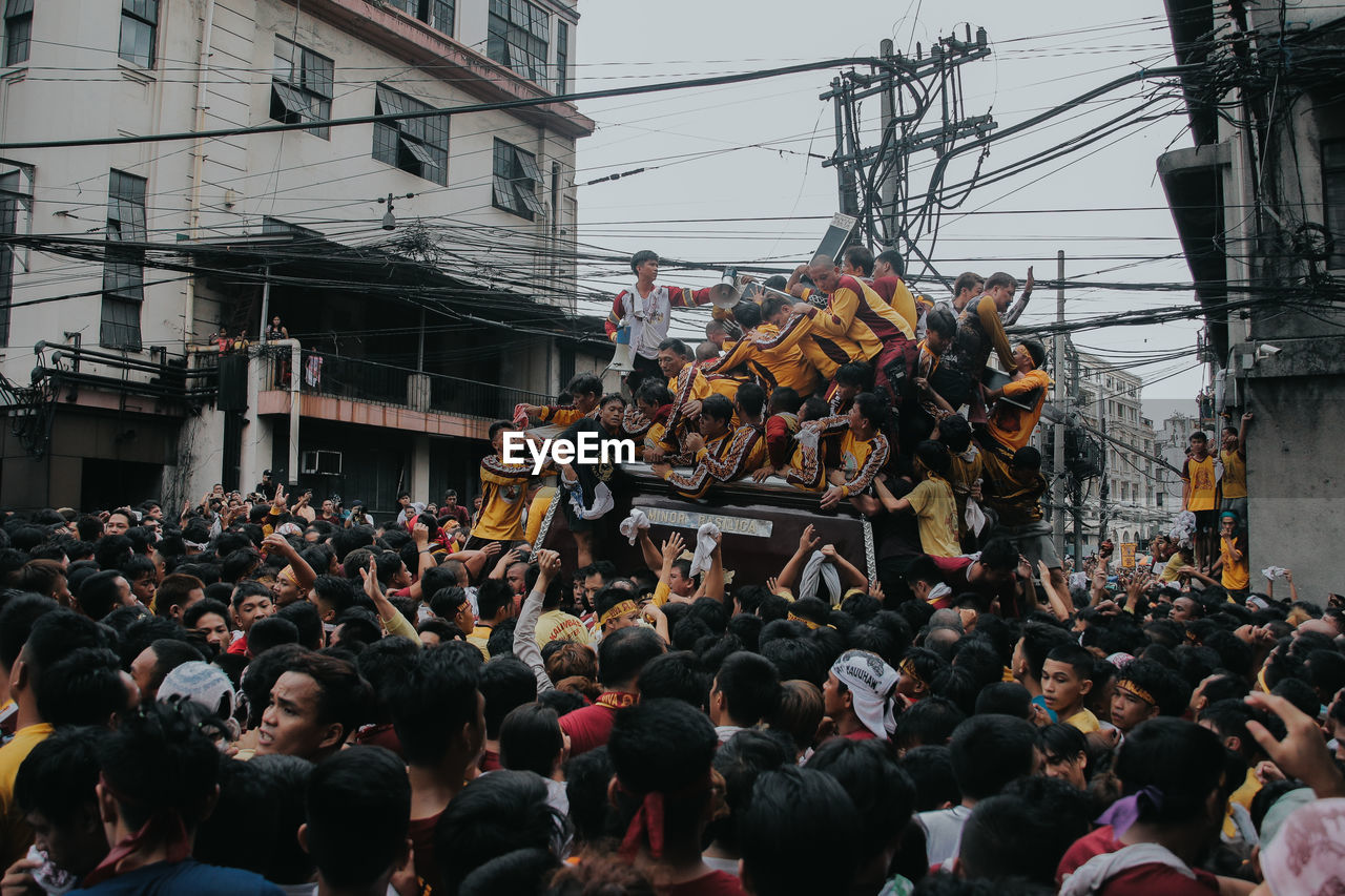 group of people, crowd, real people, large group of people, architecture, built structure, men, building exterior, city, day, street, cable, lifestyles, electricity, outdoors, occupation, power line, women, togetherness, power supply